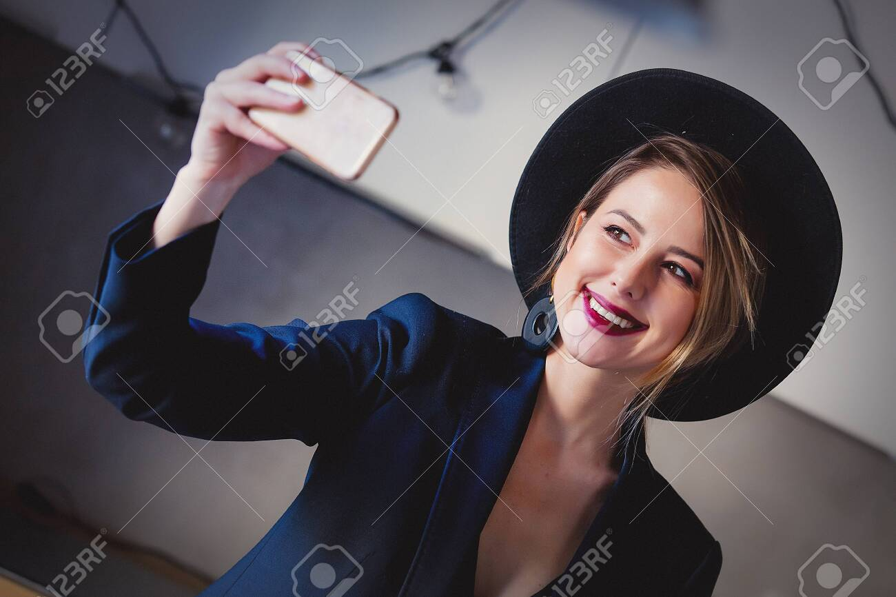 Young girl in black hat and dress and make a selfie on mobile phone. - 114464431