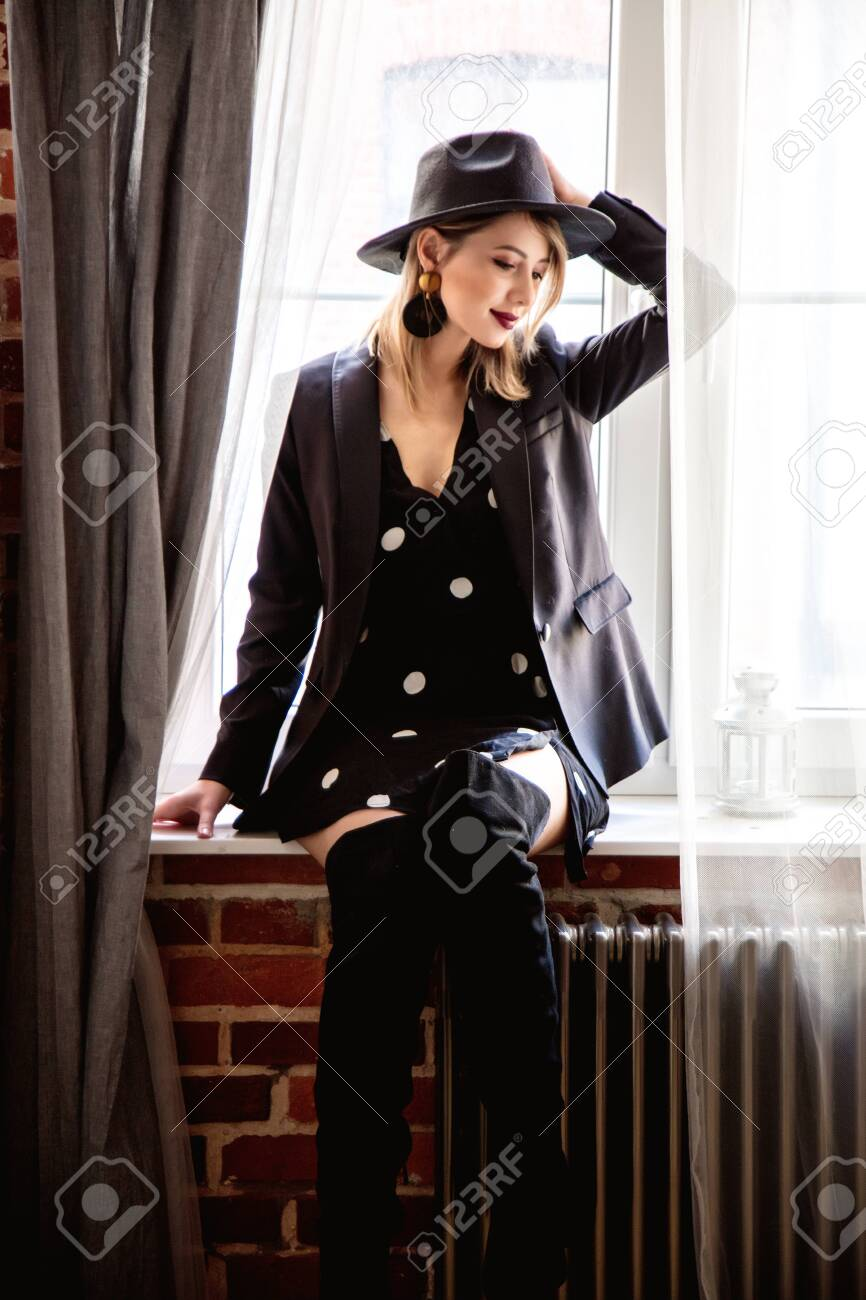 Young redhead girl in black hat and jacket with polka dot dress stay near window. - 114464426