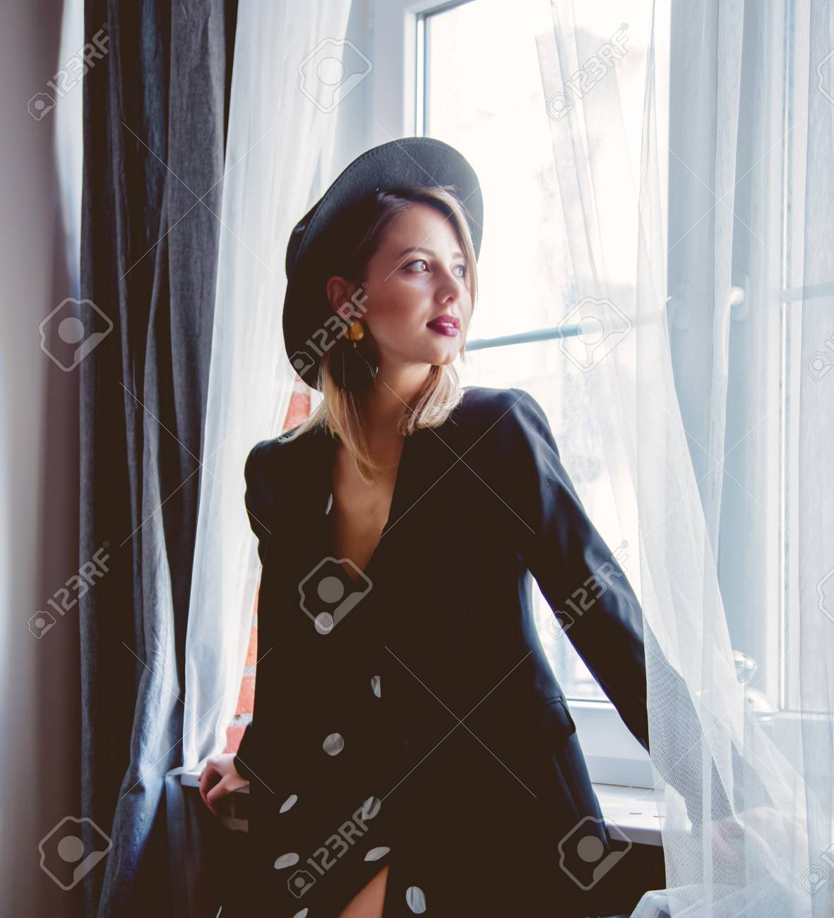 Young redhead girl in black hat and jacket with polka dot dress stay near window. - 114471199