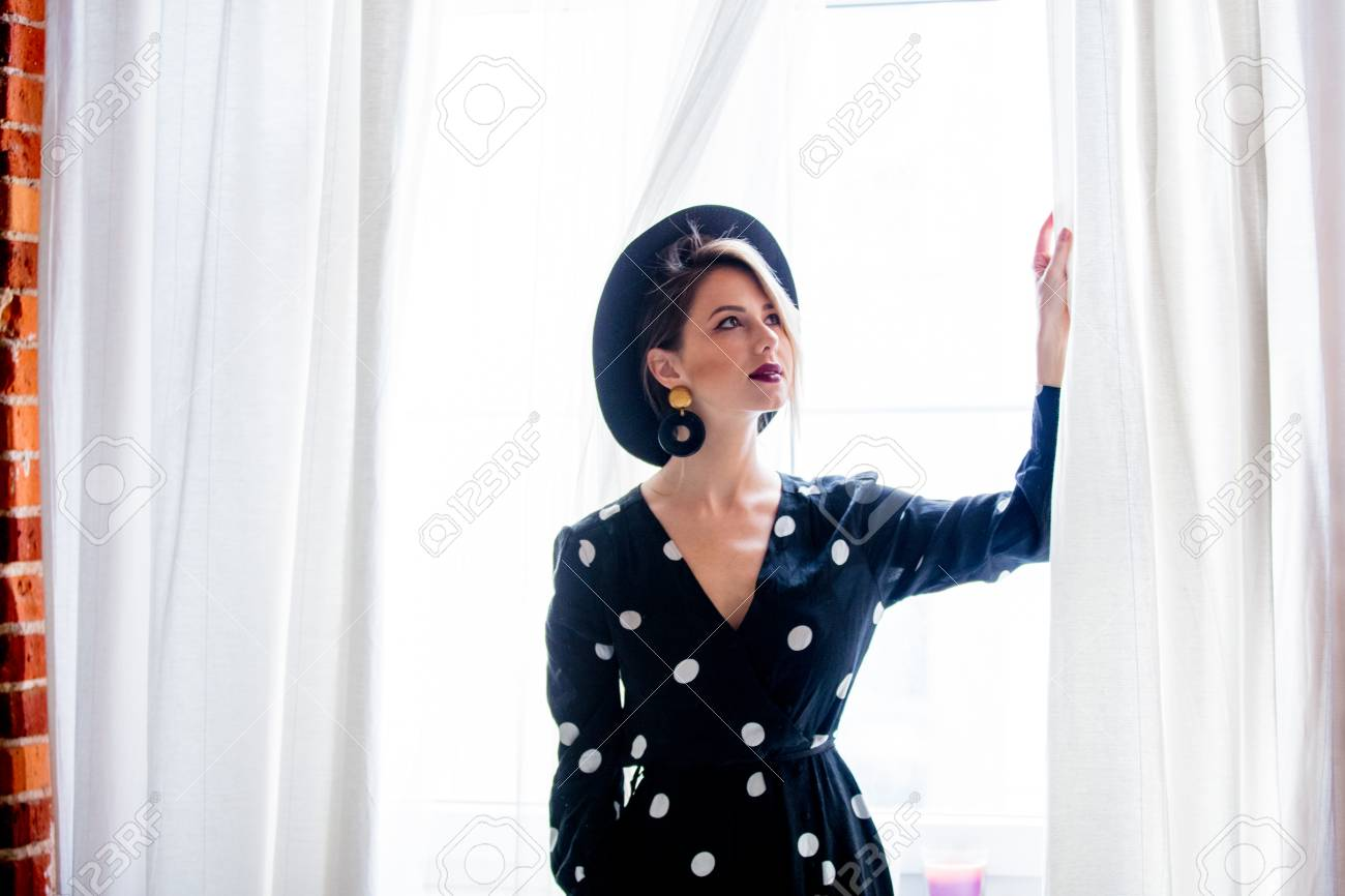 Young redhead girl in black hat and jacket with polka dot dress stay near window. - 114471365