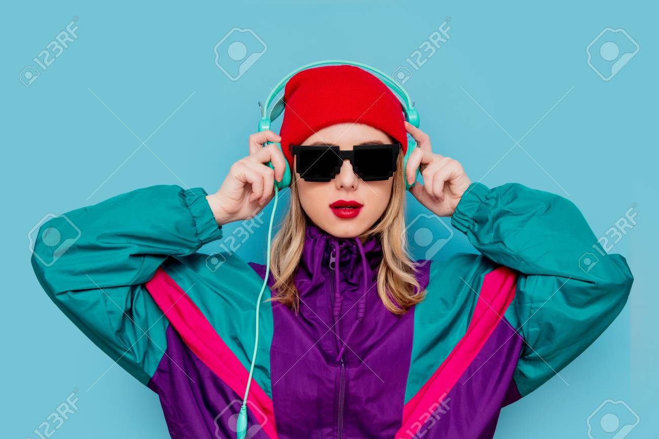 Portrait of a woman in red hat, sunglasses and suit of 90s with headphones on blue background. - 119801262