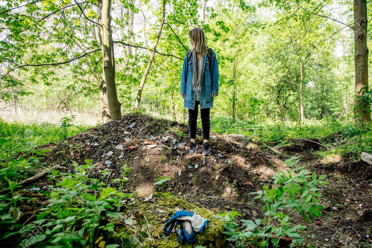 Young woman with backpack near garbage in a mixed forest Beskidy in Poland in spring time. - 122874812