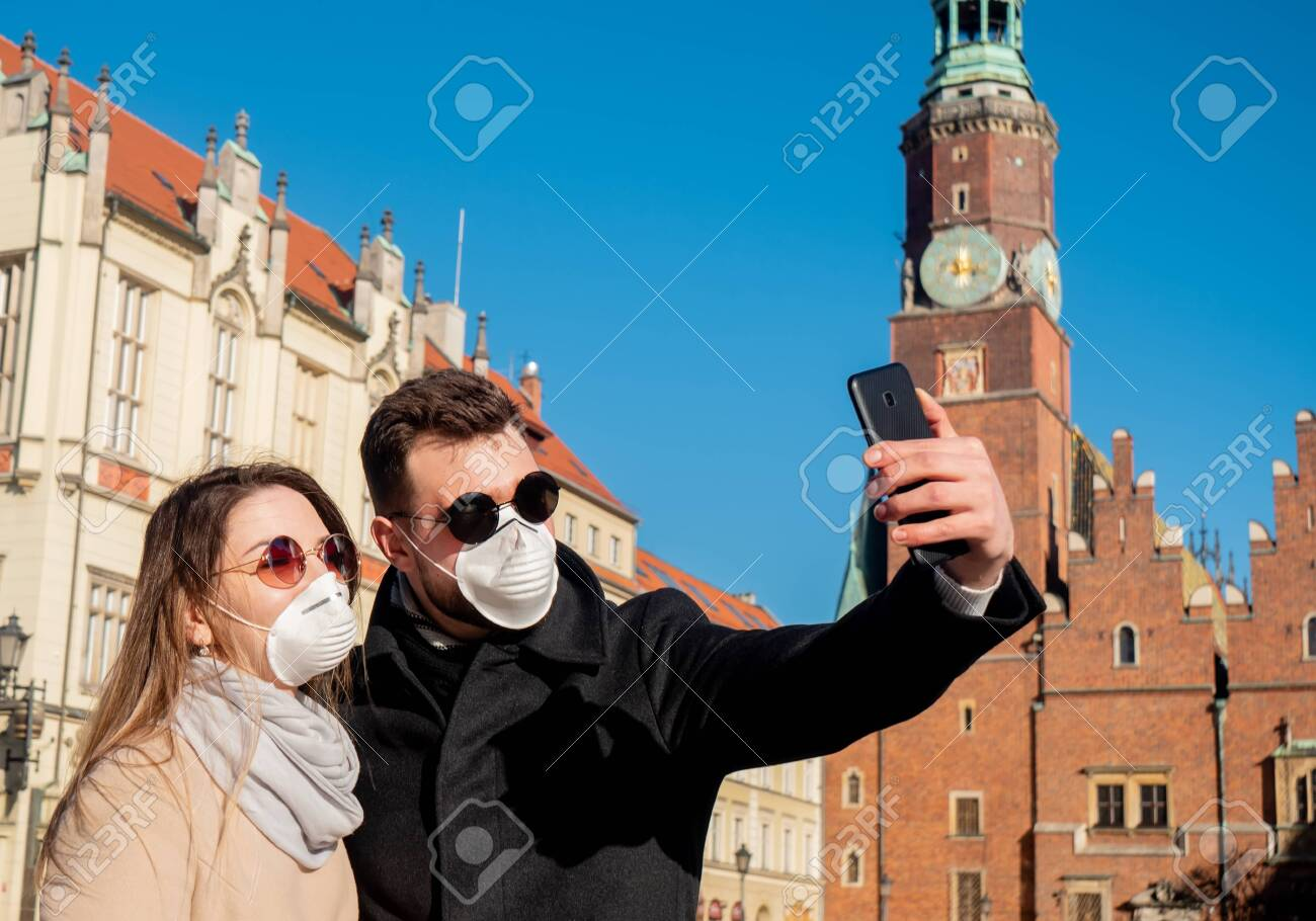 young masked couple takes a selfie in the background of a landmark in Wroclaw, Poland - 142937902
