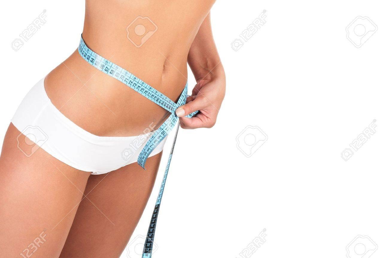 Beautiful woman measuring her waist - high key shot in studio Stock Photo - 1201833