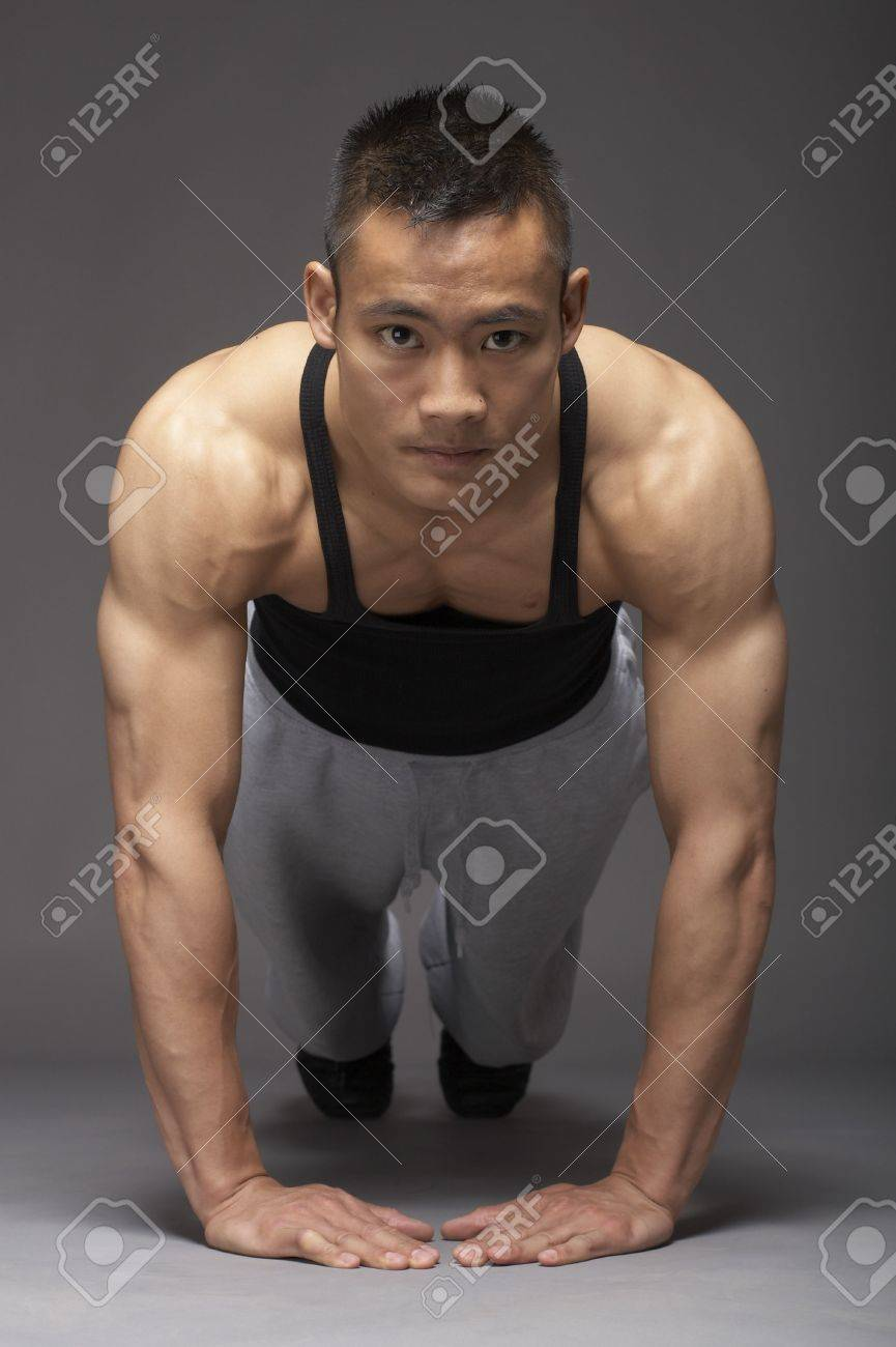 Young asian man doing pushup over gray background Stock Photo - 3111967