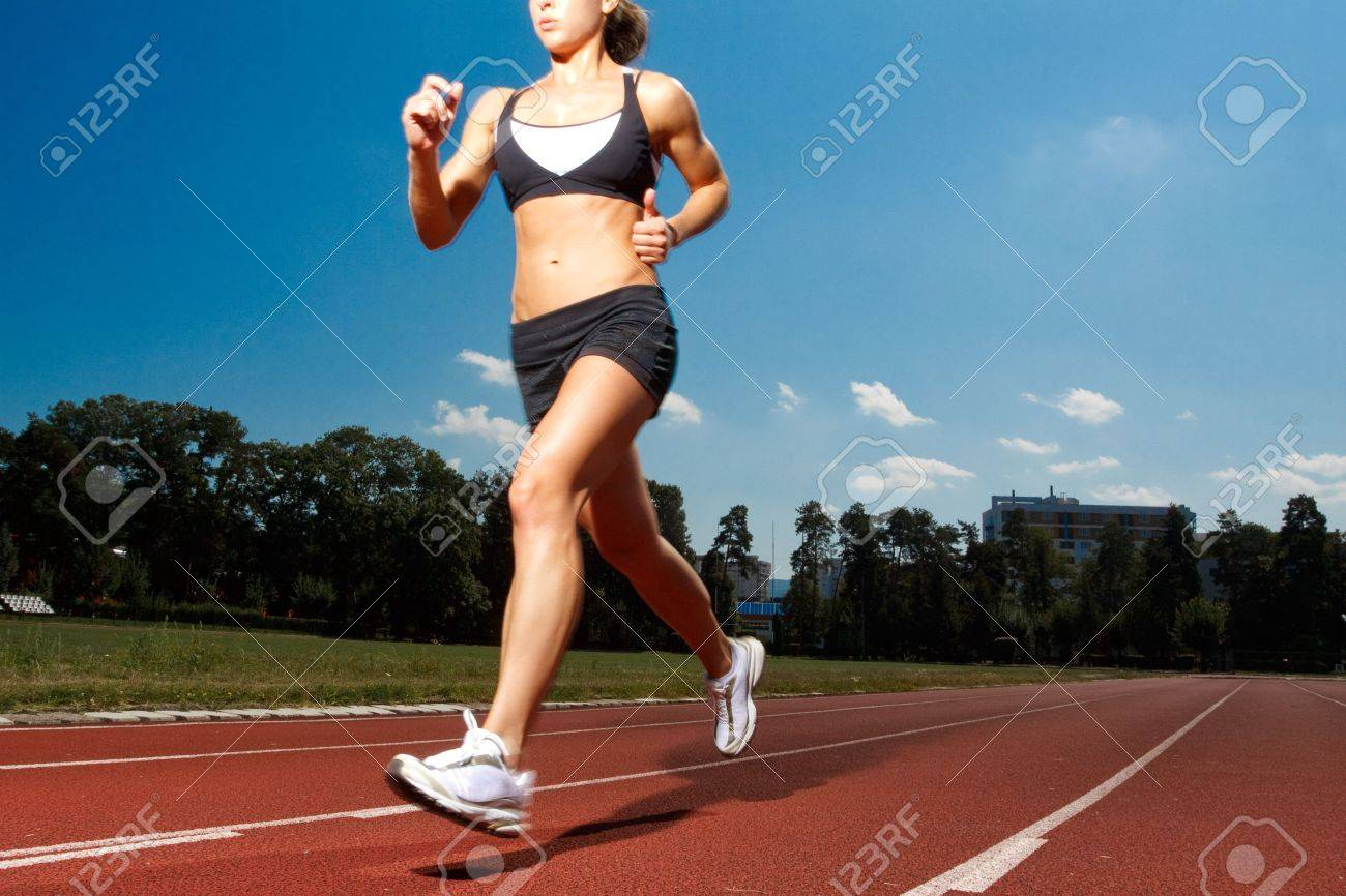 Athletic woman running on track Stock Photo - 5443076