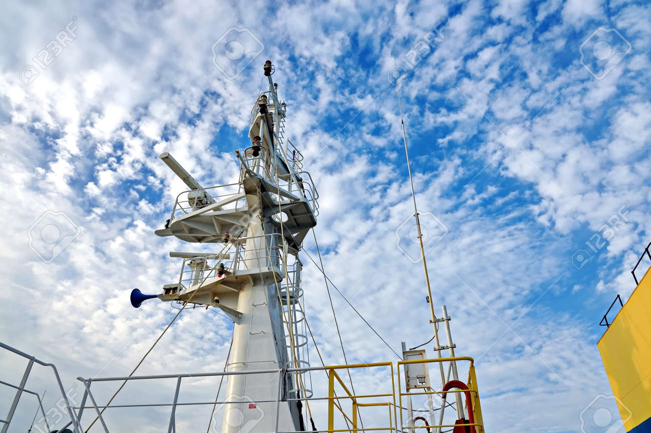 Ship structures, masts, antennas, funnel, ship wheelhouse against the blue sky and clouds. - 153480892