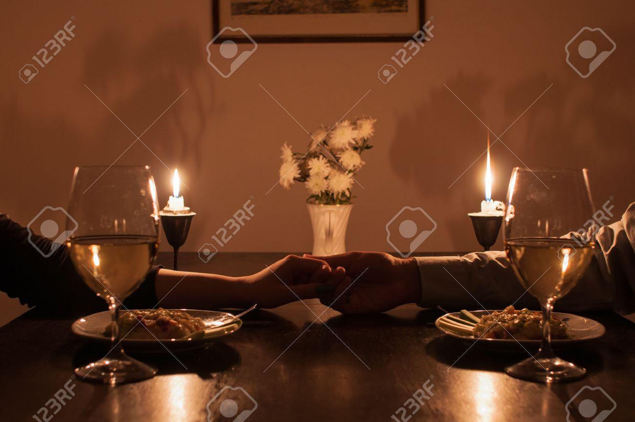 Loving couple holding hands during romantic dinner - 51681837