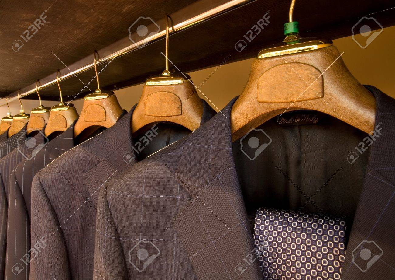 A row of designer suits hanging in a menswear store. - 8463547