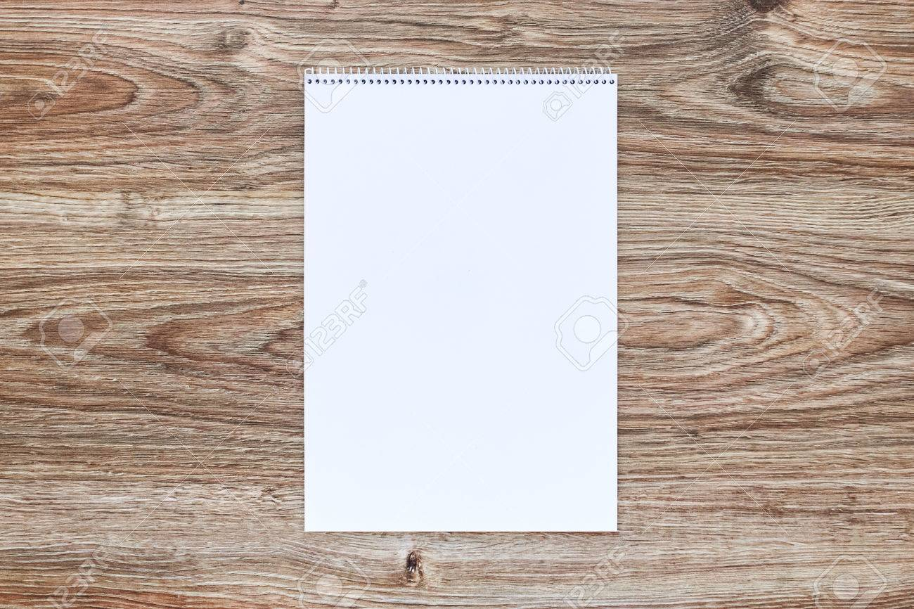Mockup of open album with blank white page on wooden background. Vertical orientation, top view. - 58454906