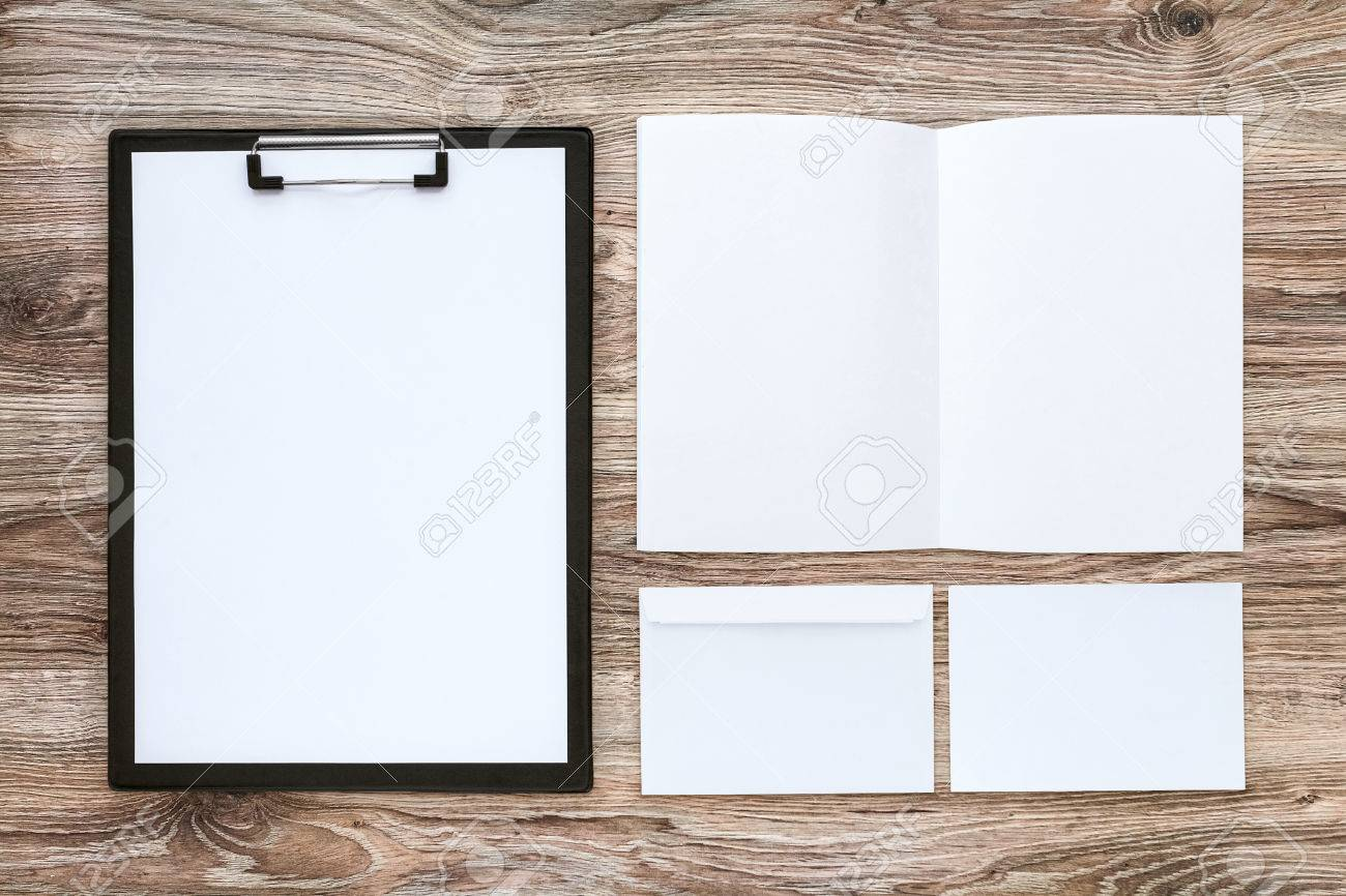 Template set of corporate identity on wooden desk. Business stationery mock-up with brochure, envelope, card, etc. Top view. - 64337503