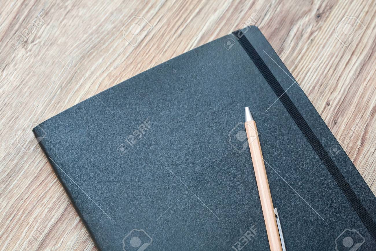 Closed classic planner with pen is on a wooden desk. Nothing extra - 85240646