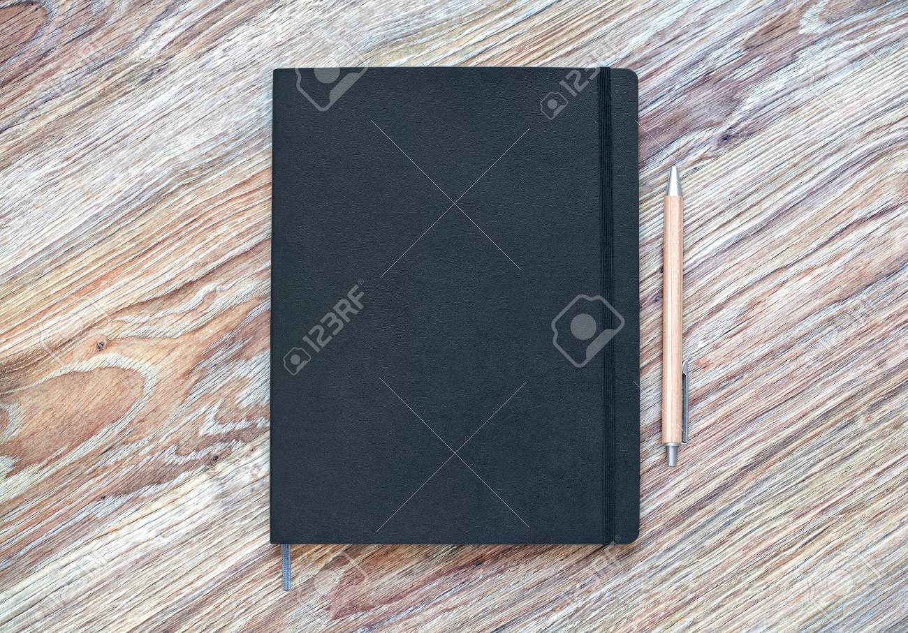 Closed classic planner with pen is on a wooden desk. Nothing extra - 85581153