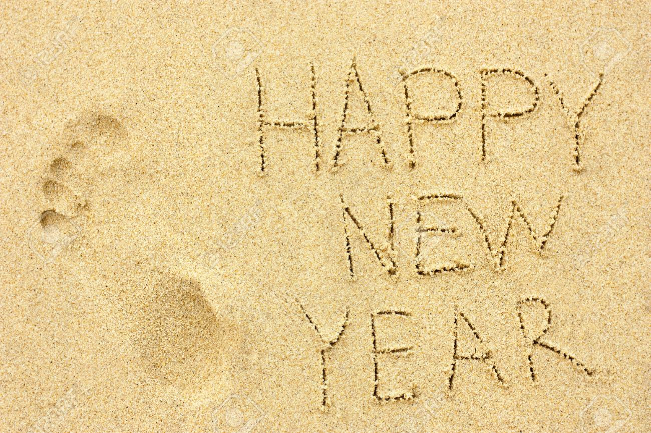 inscription happy new year and human footprint in the sand on the beach stock