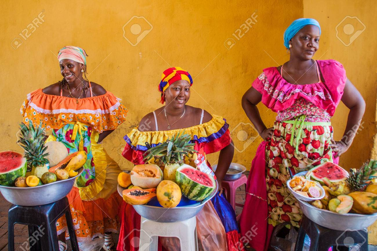 CARTAGENA DE INDIAS, COLOMBIA - AUG 28, 2015: Women wearing traditional costume sell fruits in the center of Cartagena. - 60042774