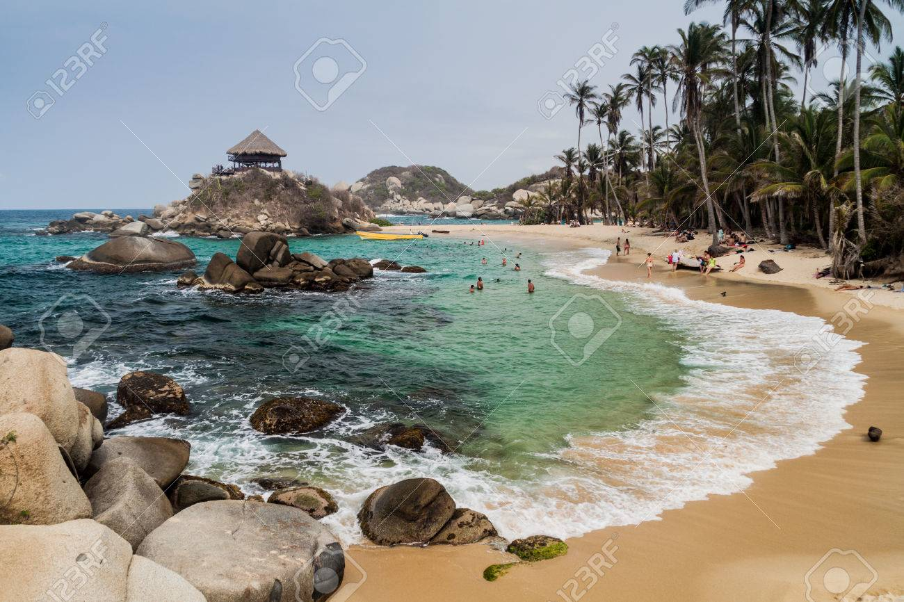 TAYRONA, COLOMBIA - AUGUST 26, 2015: People enjoy beautiful waters of Carribean sea in Tayrona National Park, Colombia - 62023282