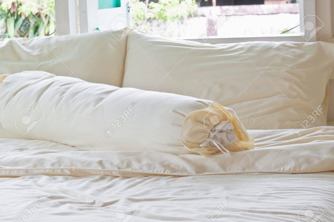 Messy bed with white pillows near windows - 13750270