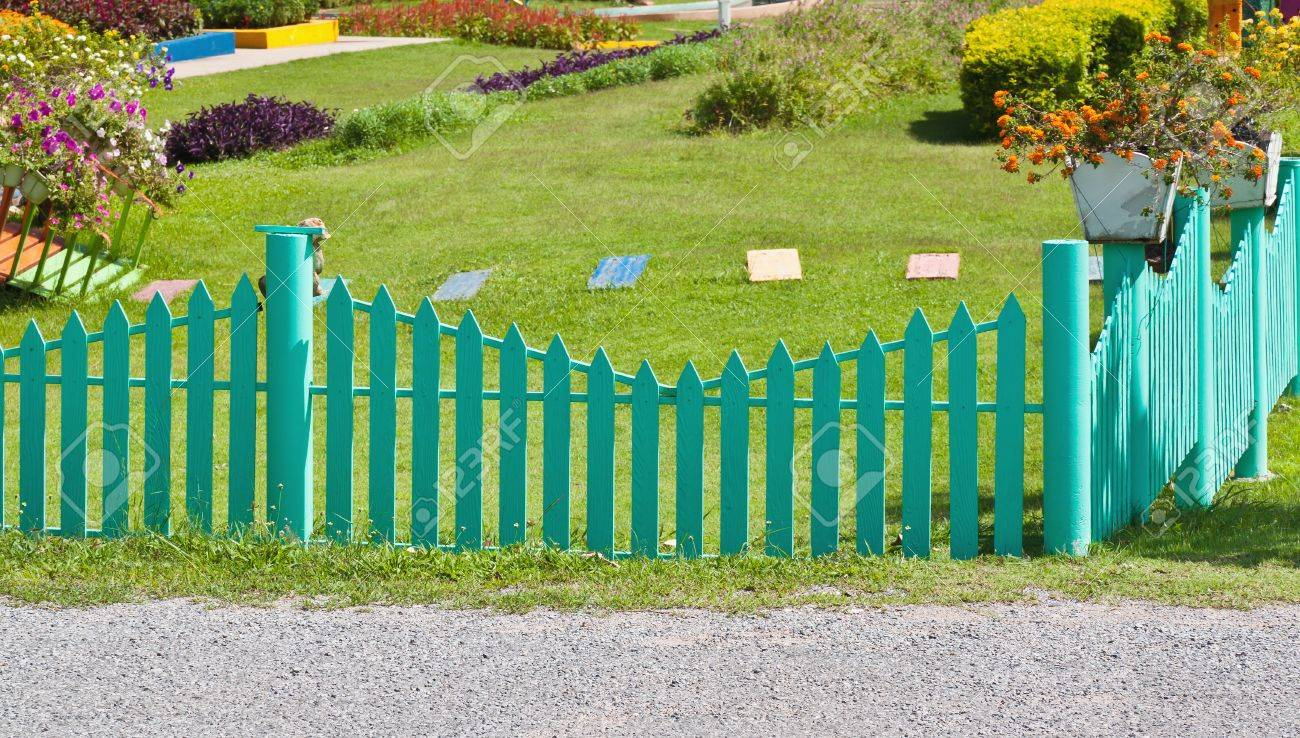Green Picket Fence With Road Green Garden And Flower Stock Photo