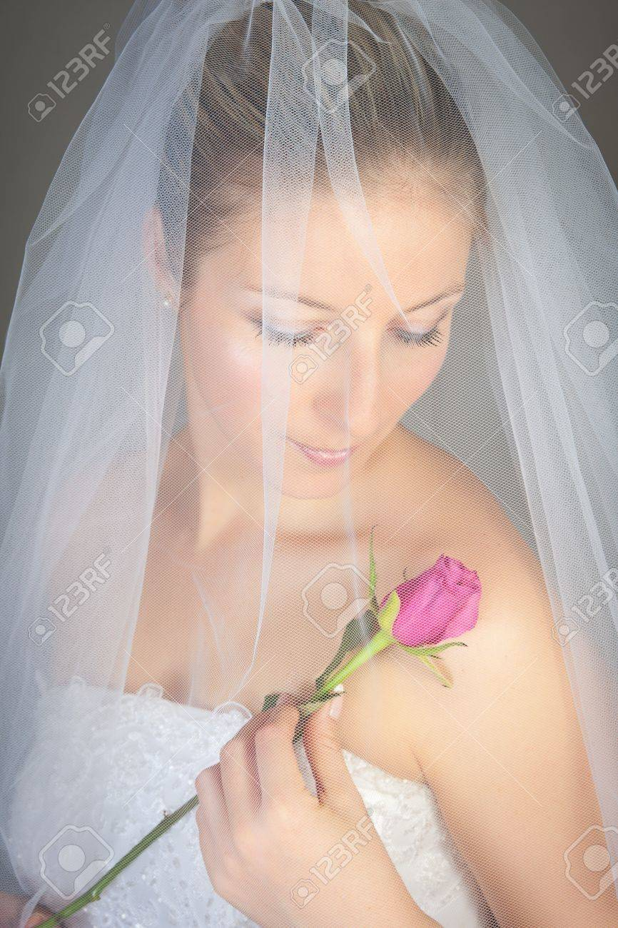 Caucasian bride posing in wedding dress and rose flower Stock Photo - 7021442