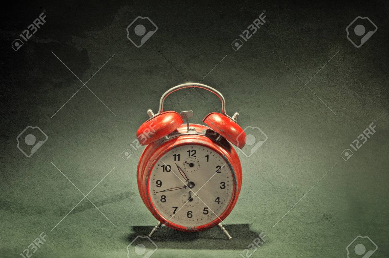 Red old style alarm clock over a grunge background Stock Photo - 17544773