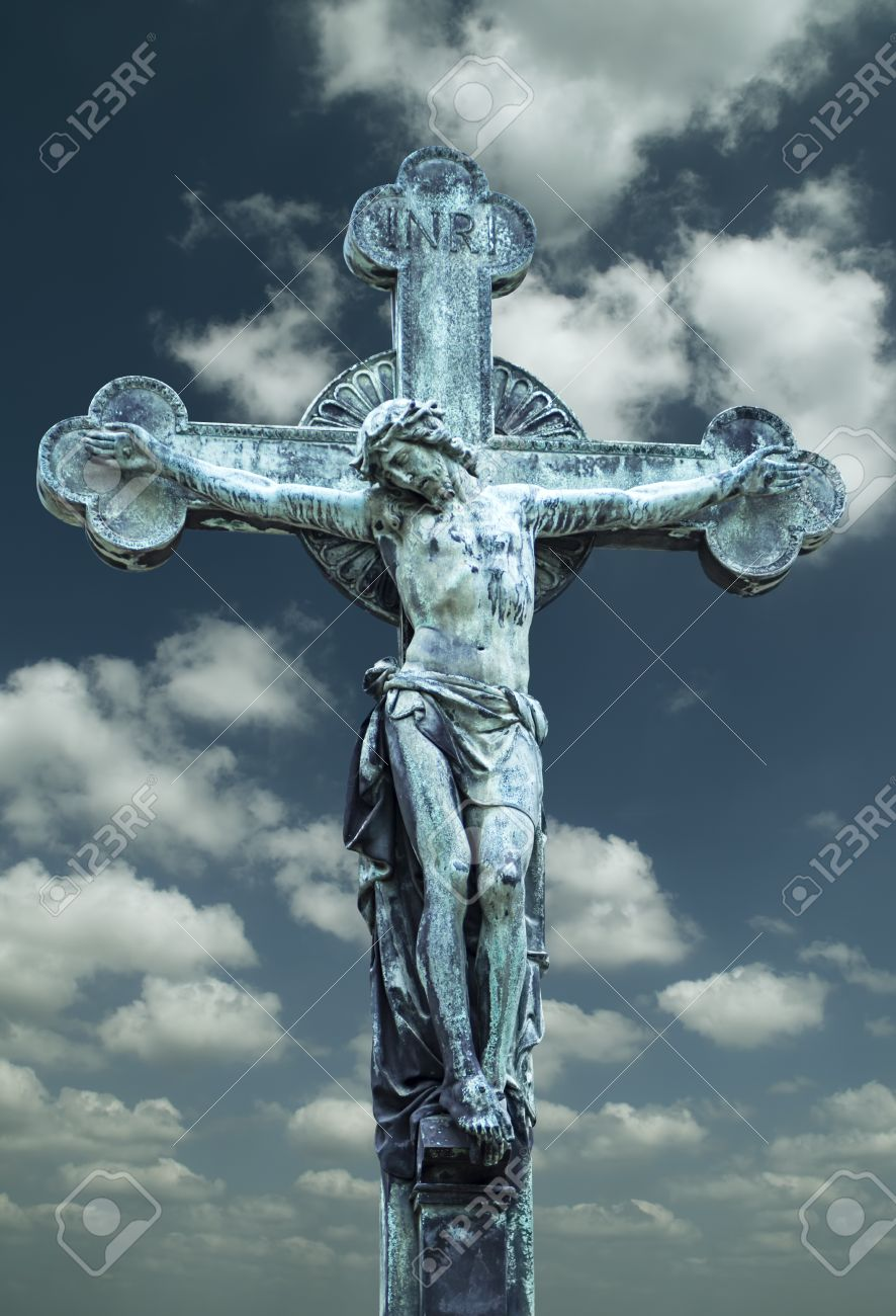 jesus christ crucifixion sculpture against dark clouds stock photo