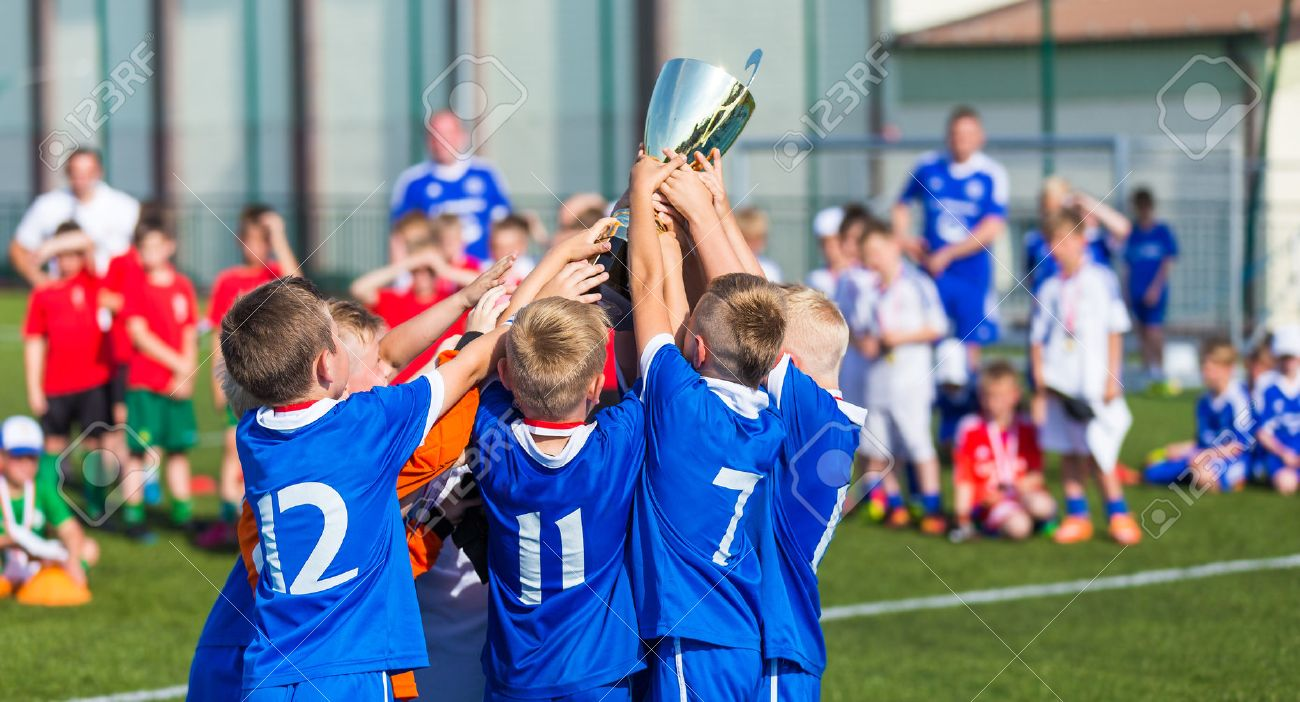 Young Soccer Players Holding Trophy. Boys Celebrating Soccer Football Championship. Winning team of sport tournament for kids children. - 51866247