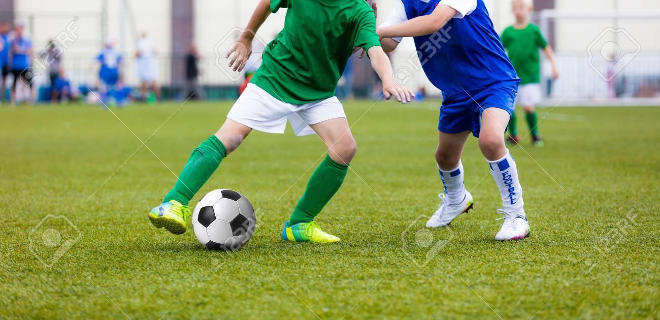5b116328d4fd8 Foto de archivo - Jóvenes muchachos jugando fútbol juego de fútbol en el  campo de deportes. Ejecución de jugadores de fútbol en las camisas de  deporte.