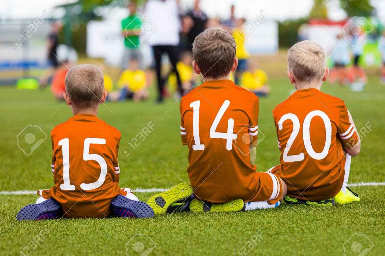 65717f1b3b72 Kids of young soccer football team. Boys in orange shirts as reserve  players sitting on