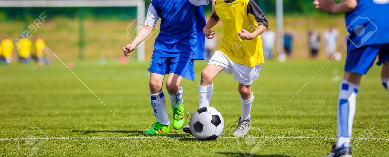 39962d384dd6b Foto de archivo - Niños jugando fútbol juego de fútbol en el campo de  deportes. Muchachos que golpean con el pie el balón de fútbol.