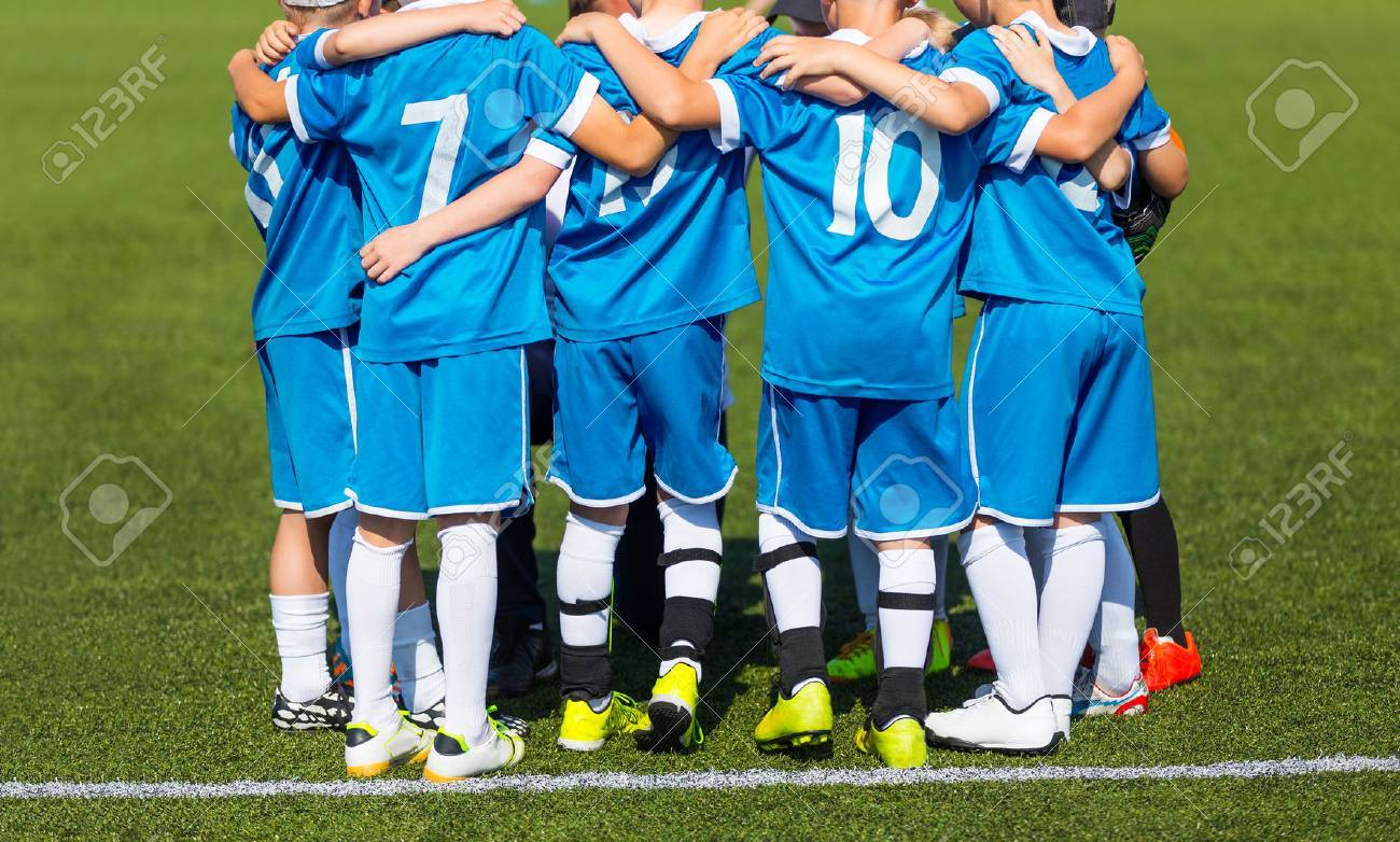 Kids with soccer coach gathering before match. Youth soccer football team. Group photo. Soccer players standing together united. Soccer team huddle. Teamwork, team spirit and teammate example. - 62310100