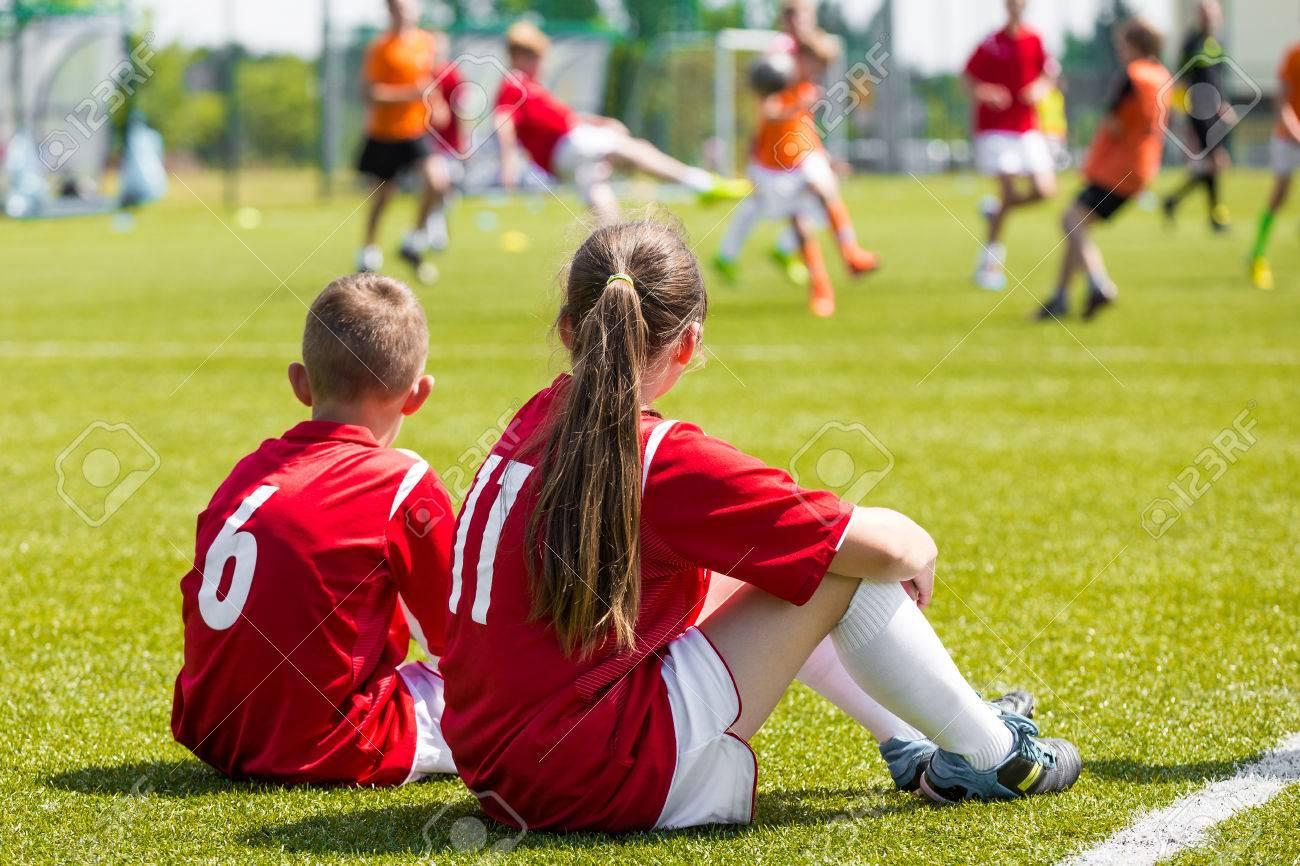 996c4b0ae1f4e Foto de archivo - Niños jugadores de fútbol que juegan al juego. Los  jóvenes jugadores de fútbol niña y niño sentados juntos en el campo de  fútbol de hierba
