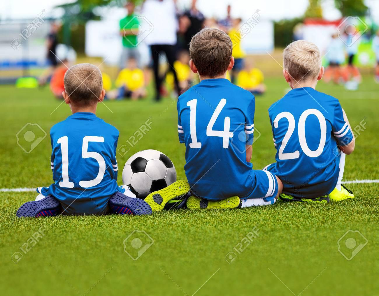46516a2e3d75f Foto de archivo - Niños en azul ropa deportiva sentado en Soccer Pitch y  viendo fútbol Partido de fútbol. Torneo de Fútbol de niños.