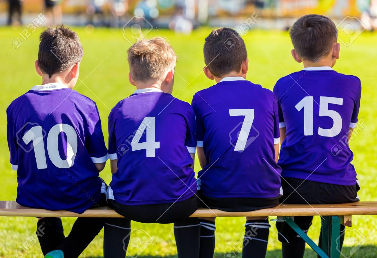 Equipo De Deportes Para Niños. Young Boys Sentado En El Banco De ...