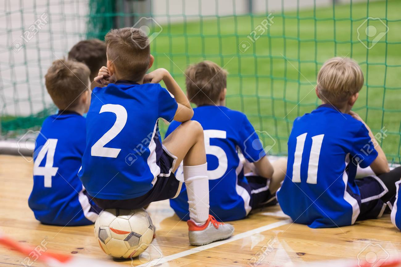 52ea7bd6172 Children futsal team. Group of young indoor soccer players sitting  together. Kids school football