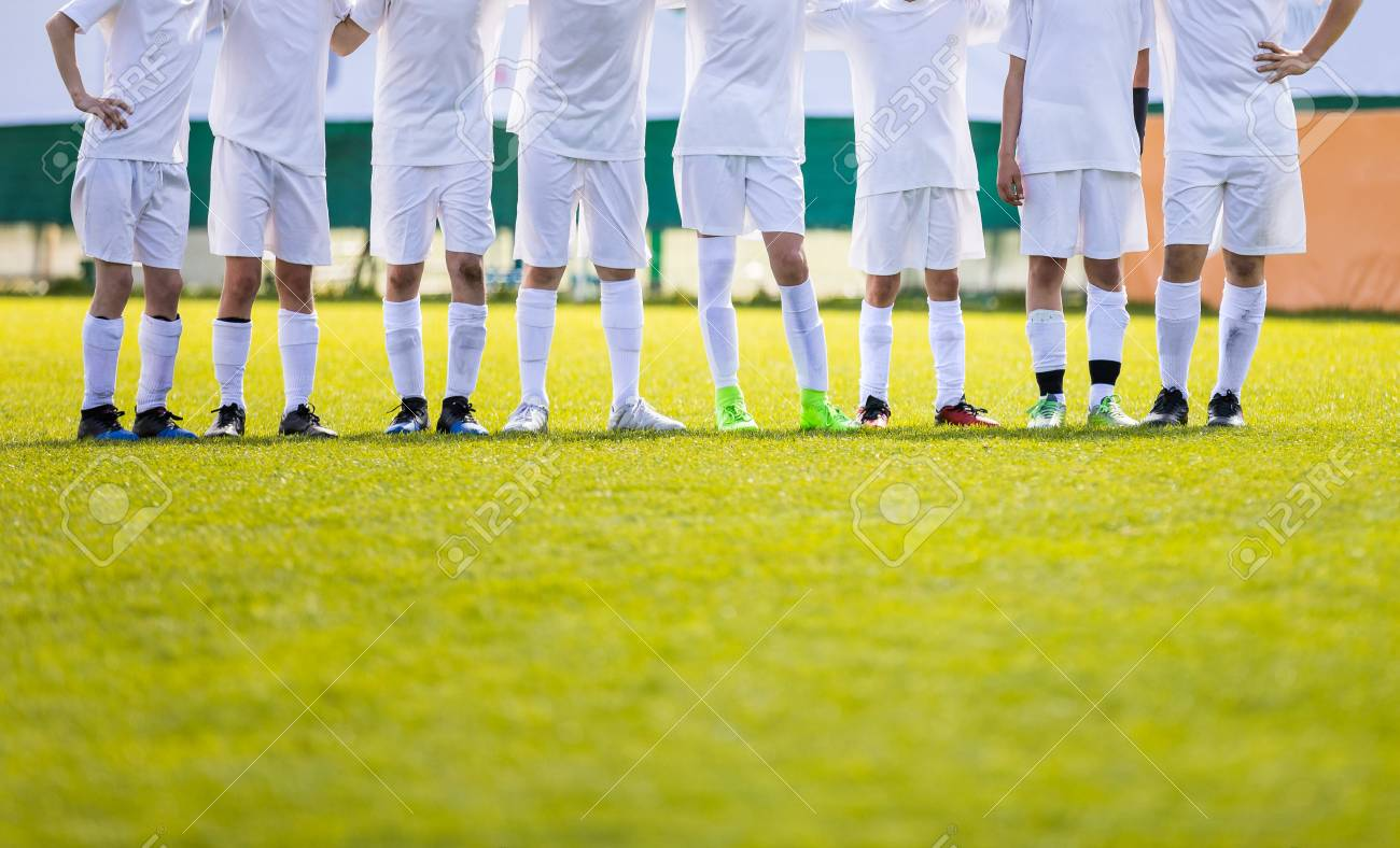 Youth Football Team. Young Soccer Players Standing in Row. Boys Standing Together During Penalty Shots. Boys in White Soccer Jersey Shirts - 100931324