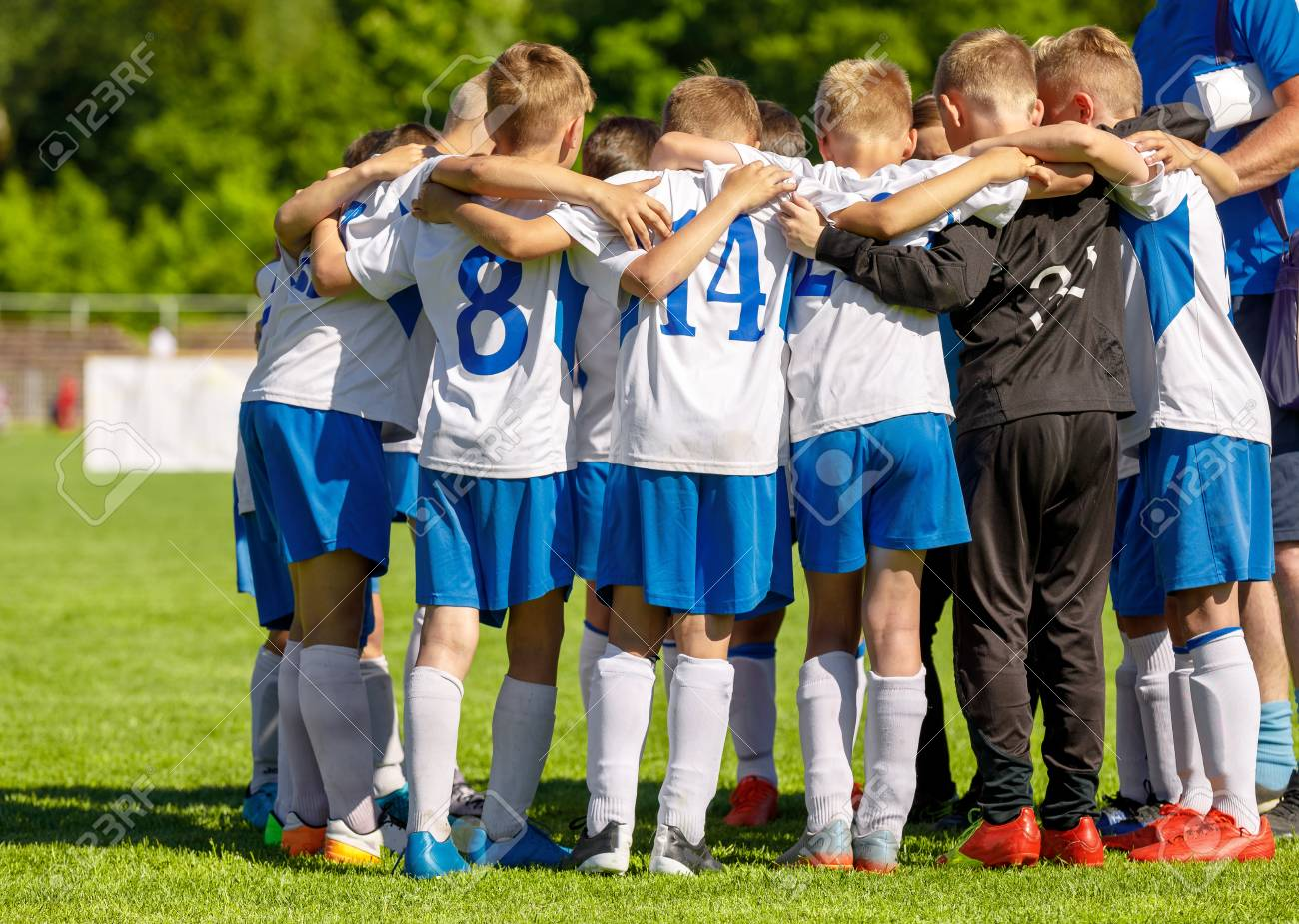 Football Youth Team Huddling with Coach. Young Happy Boys Soccer Players Gathering Before the Final Match - 125674436