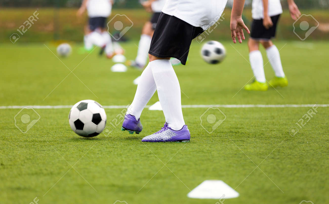 Soccer Player Kicking Ball on Training. Group of Footballers Improving Skills on Practice Venue. Soccer Boy in Purple Cleats and White Soccer Jersey Kit - 165729935