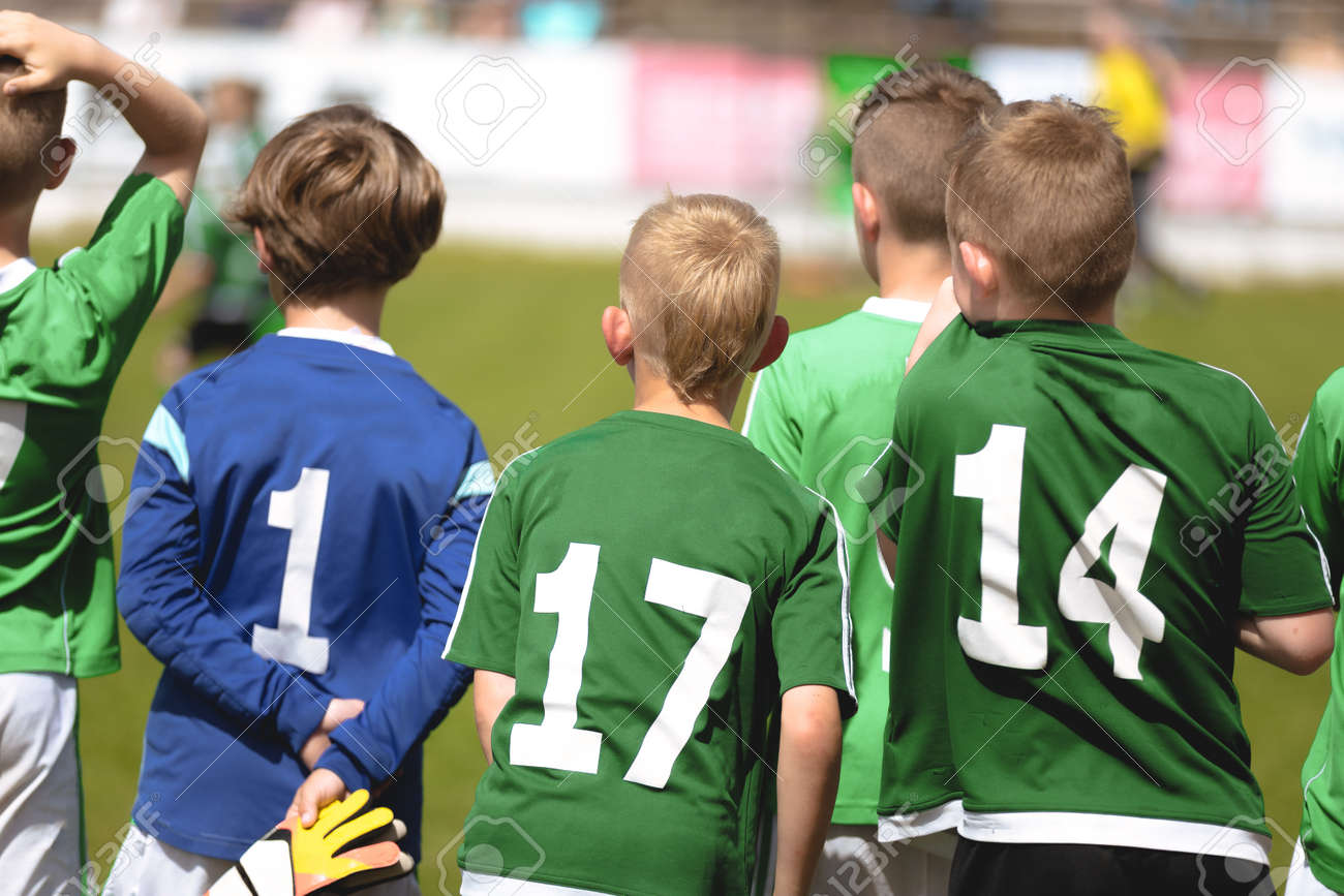 Boys in Green Soccer Jersey Shirts Standing in a Team and Watching Football Tournament Match. Kids Playing Sports Outdoor in Summer Sunny Day - 168091075