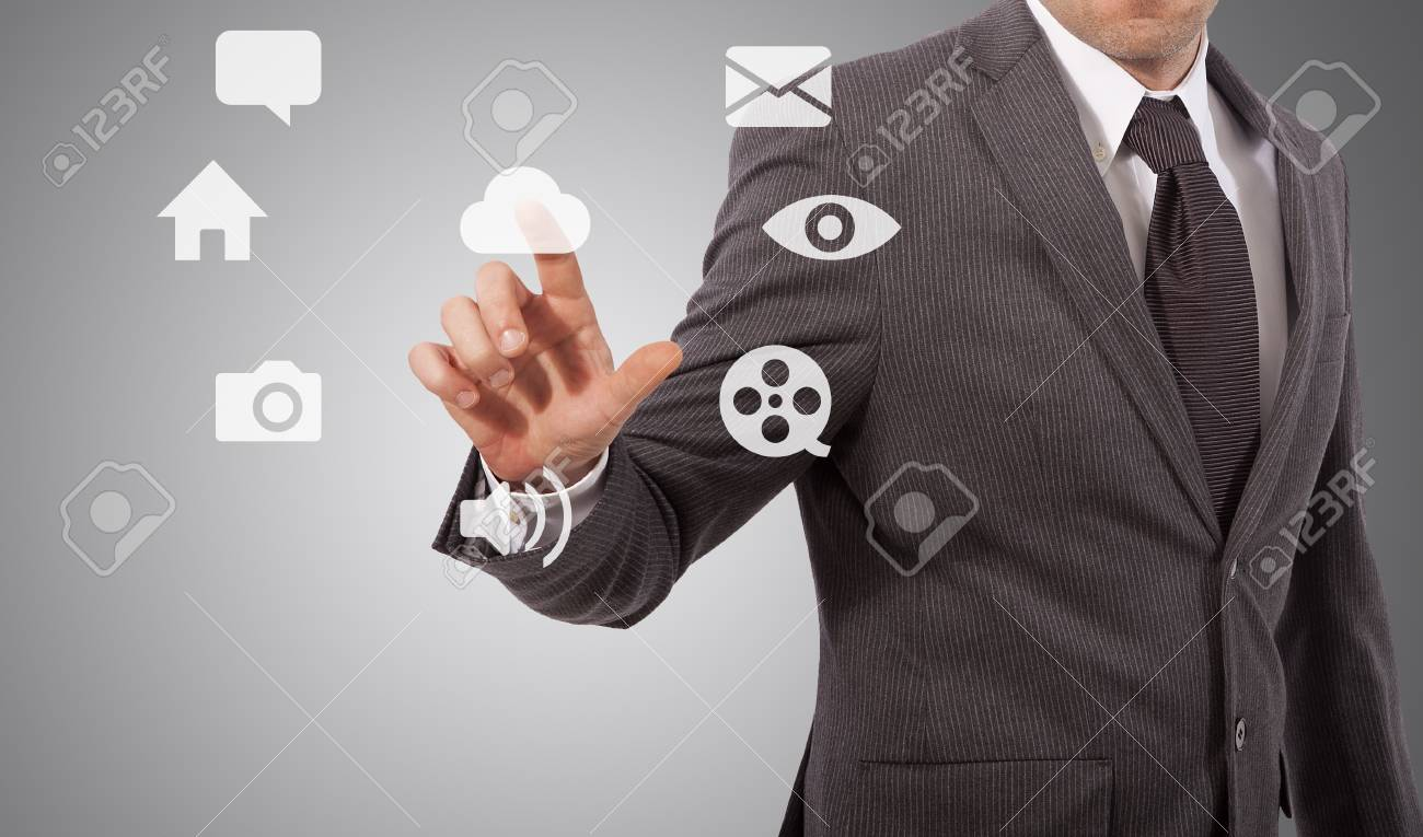 business man touching icons on screen, grey background Stock Photo - 17961924