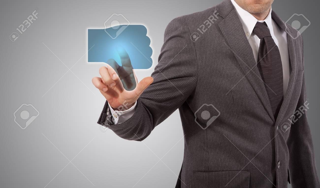 Businessman Presses a dislike Button, grey background Stock Photo - 18650112