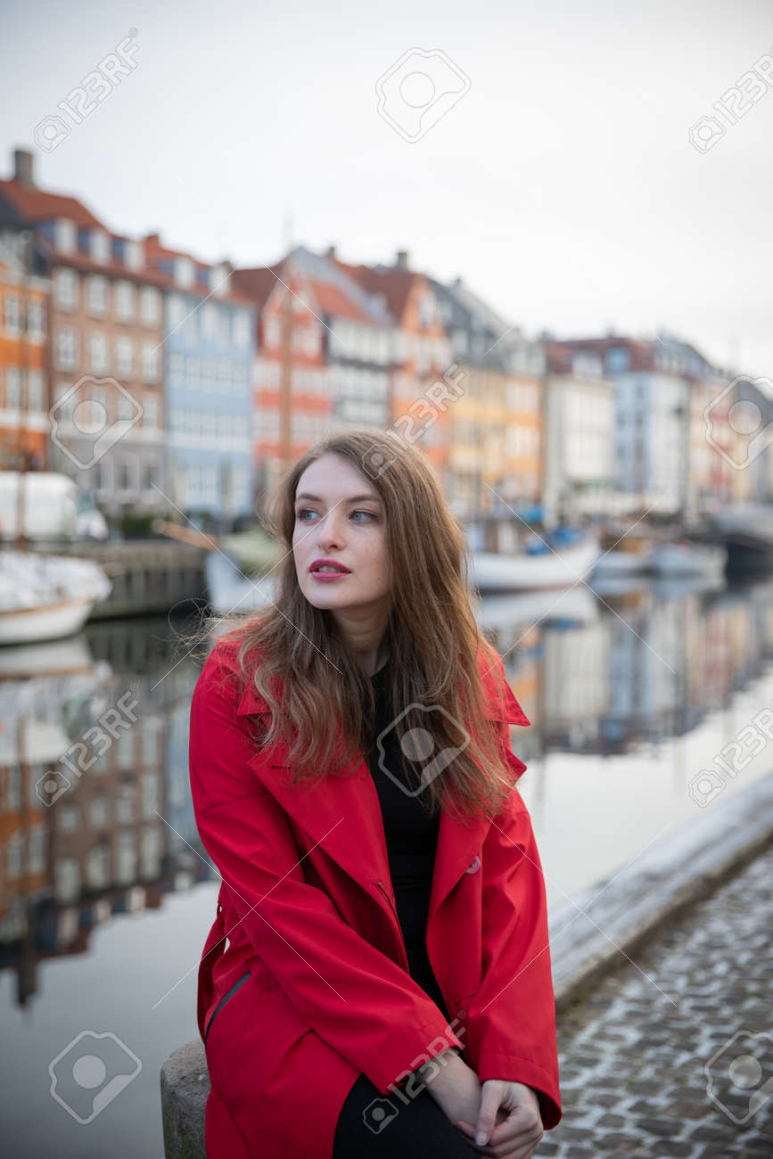 Attractive girl sitting, she is a tourist and is visiting Nyhavn in Copenhagen, Denmark. She is wearing a red coat. - 166160707