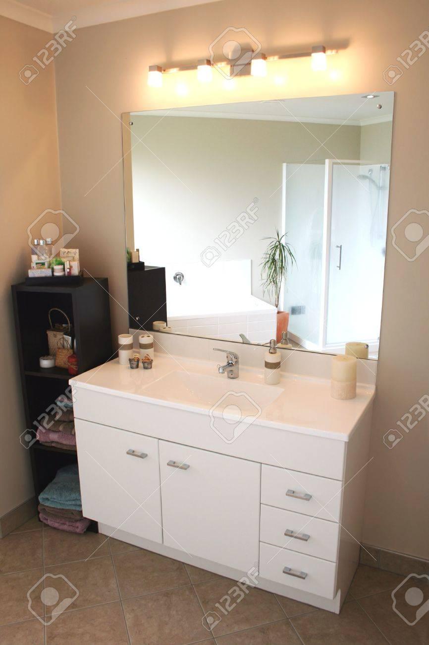 Une vanité de salle de bains moderne blanc et en acier inoxydable, miroir  et accessoires.