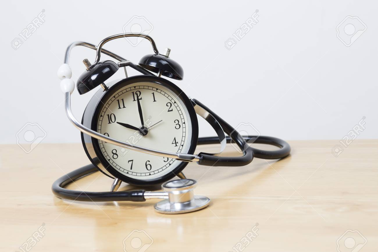 stethoscope and bell alarm clock on wooden table stock photo