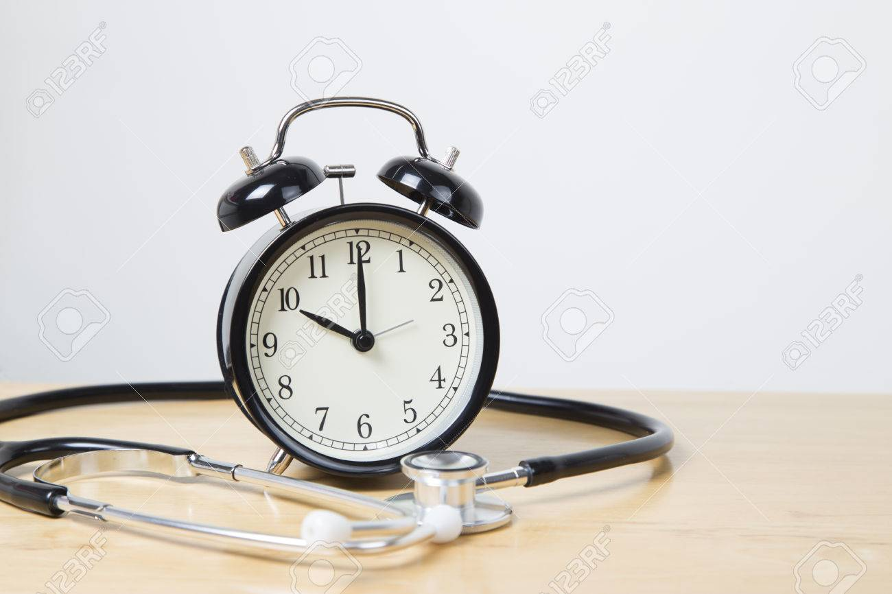 black bell alarm clock in cente of stethoscope stock photo picture