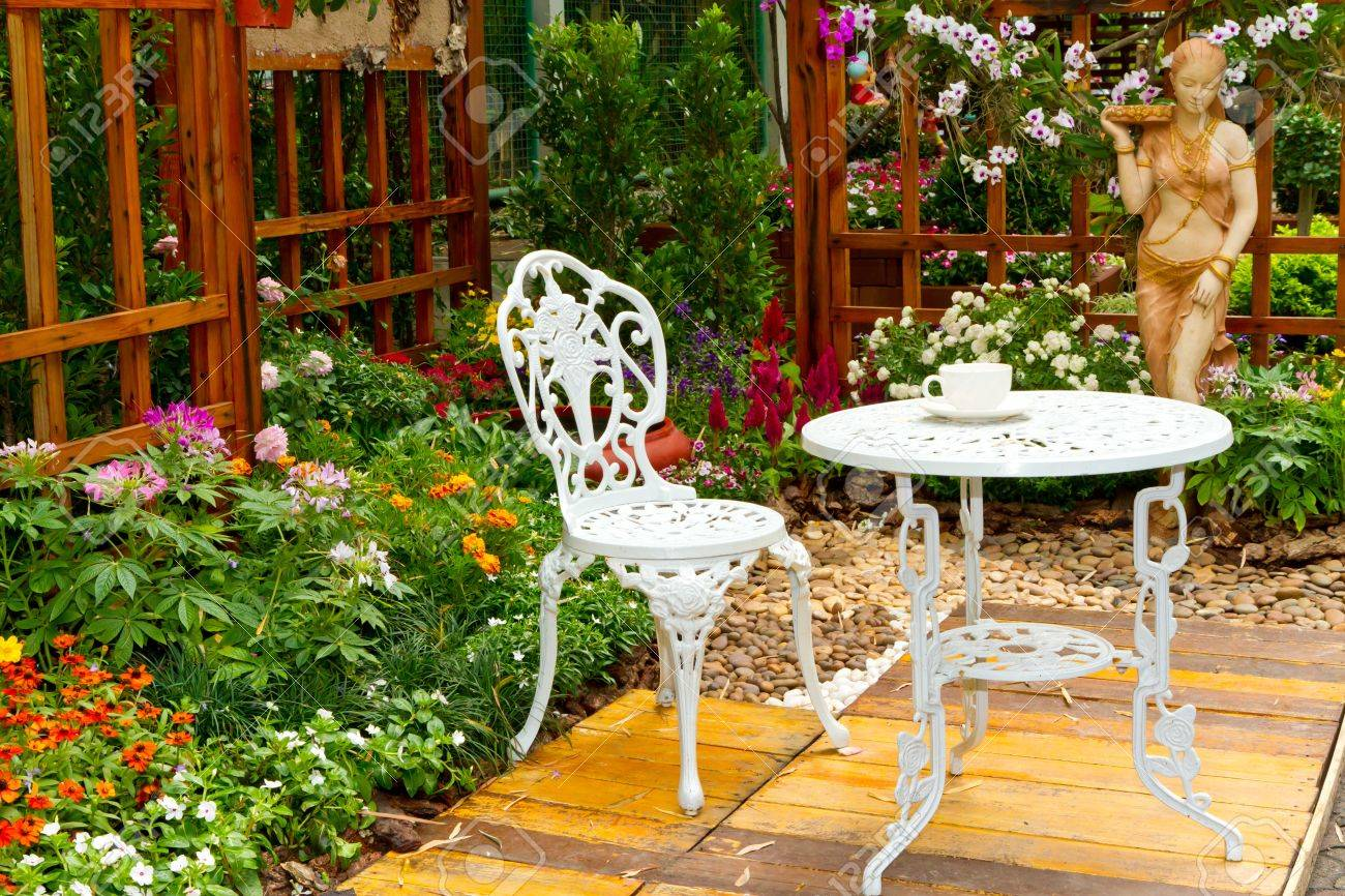beautiful garden with white table and chair stock photo 13244779