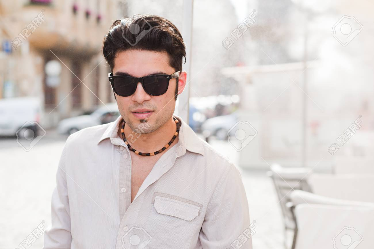 attractive man wearing sunglasses looking cool on the street Stock Photo - 16865378