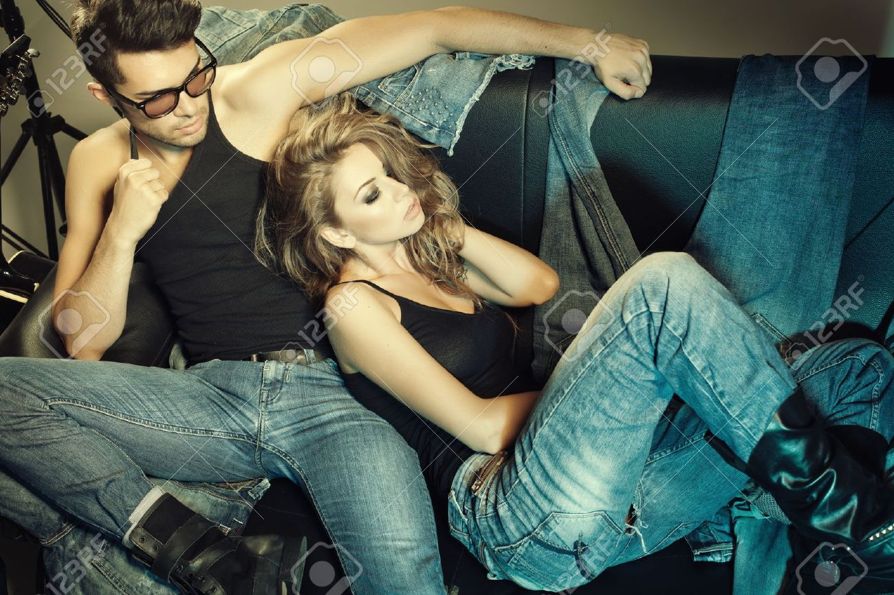 Sexy man and woman dressed in jeans doing a fashion photo shoot in a professional studio Stock Photo - 16867046