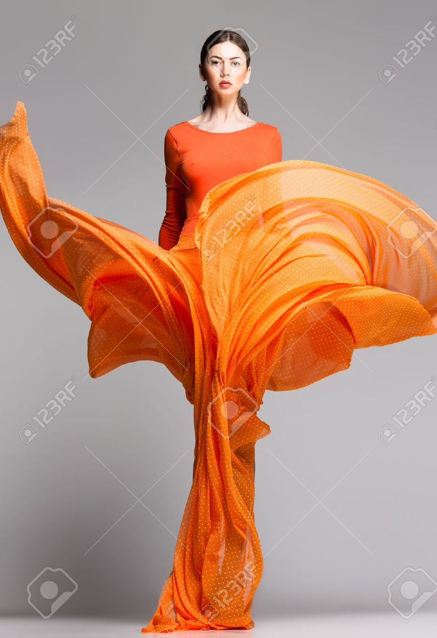 Beautiful Woman In Long Orange Dress Posing Dynamic In The Studio ...