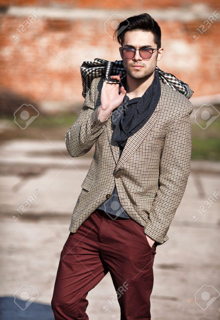 セクシーなファッションの男性モデルは屋外ポーズ袋を保持してエレガントな服