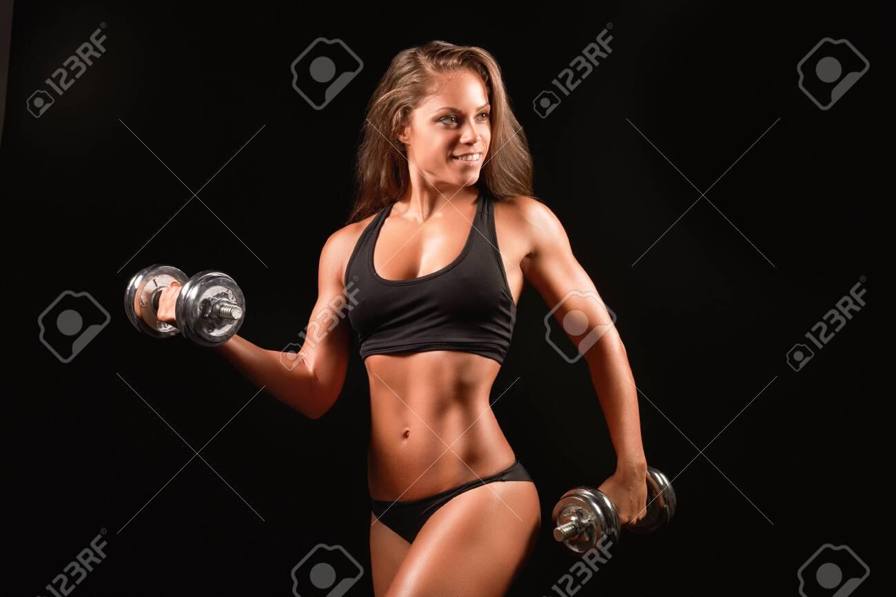 Closeup photo of a sports woman portrait wearing black sportswear over dark lifting dumbell - 154670115